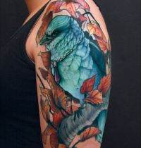 Bluebird among leafs tattoo