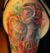 Owl among roses tattoo