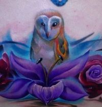 Owl among flowers tattoo