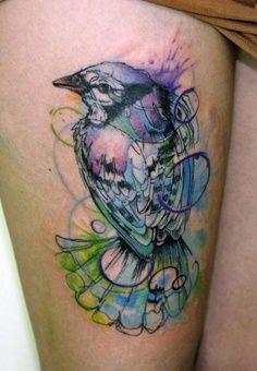 Colourful bird tattoo on leg