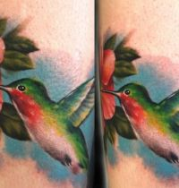 Tattoo with hummingbird green and ornage.