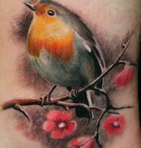 Ankle tattoo with bird and flowers