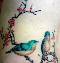 Green and white birds tattoo