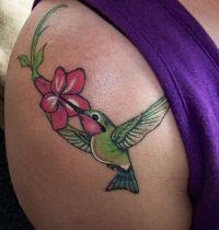 Green hummingbird and flower tattoo