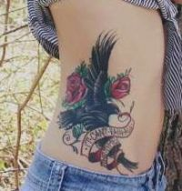 Black bird with red roses tattoo