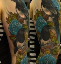 Magpies among blue roses tattoo