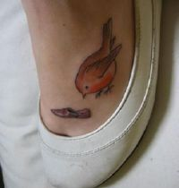 Orange bird tattoo on foot