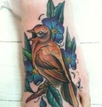 Foot tattoo with bird and blue flowers